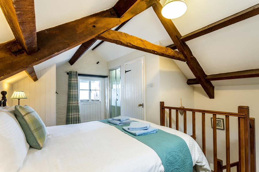 double bed with towels and wooden beams