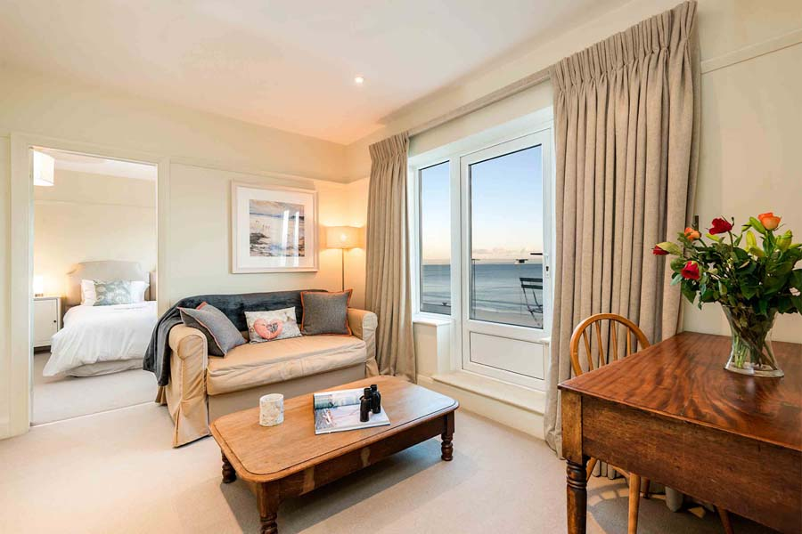sofa next to bedroom with sea views and flowers on table