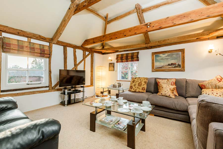 cottage interior with sofas and coffee table and wooden beams