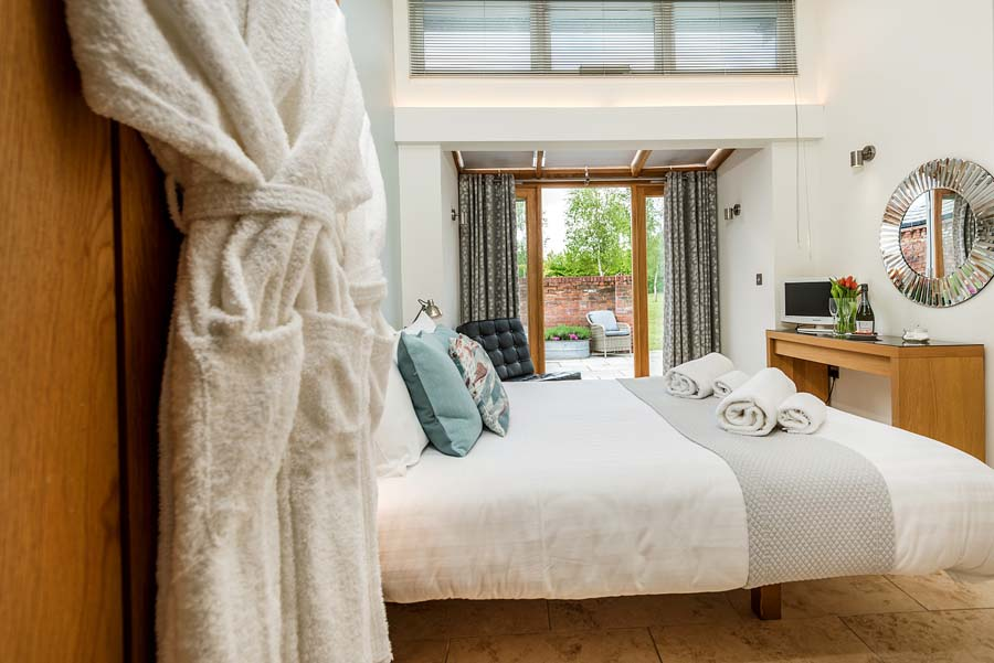 bedroom with bathgown and towels leading to garden
