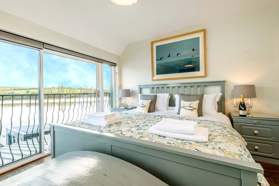 bedoom with picture on wall and towels overlooking a view of a river